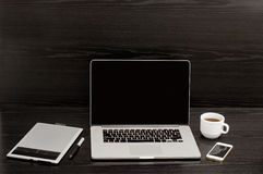 Abra o portátil, a caneca de café, um telefone e uma tabuleta de gráficos em um fundo preto Imagens de Stock Royalty Free