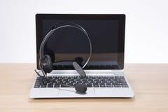 Abra o portátil com uns auriculares equilibrados no teclado Imagens de Stock Royalty Free