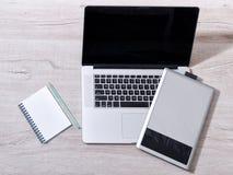 Abra o portátil, a tabuleta de gráficos e o bloco de notas com pensil em uma tabela clara, vista superior Fotos de Stock