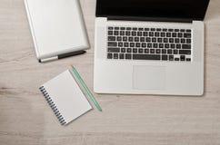 Abra o portátil, a tabuleta de gráficos e o caderno com lápis em uma tabela clara, vista superior Fotografia de Stock