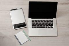 Abra o portátil, a tabuleta de gráficos e o caderno com lápis em uma tabela clara, vista superior Imagem de Stock Royalty Free
