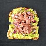 Abra o sanduíche do abacate com o atum contra a ardósia escura Foto de Stock Royalty Free