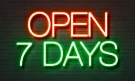 Abra o sinal de néon de 7 dias no fundo da parede de tijolo imagem de stock royalty free