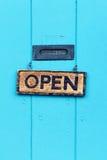 Abra o sinal na porta de turquesa fotografia de stock royalty free
