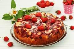 Abra a torta com as morangos situadas em uma placa em um fundo branco imagem de stock royalty free