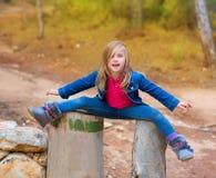 Abra troncos da menina ou de árvore das crianças dos pés na floresta Imagens de Stock