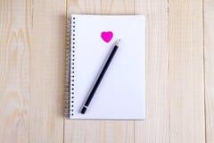 Abra um bloco de notas vazio e um coração cor-de-rosa Foto de Stock