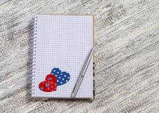 Abra um bloco de notas vazio e um coração de papel na tabela de madeira branca Fundo do dia do Valentim Espaço livre para o texto Fotos de Stock Royalty Free
