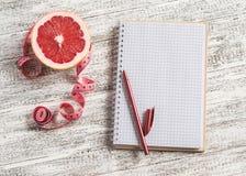 Abra um bloco de notas vazio, uma toranja e uma fita de medição em uma tabela de madeira clara O conceito da nutrição saudável, d fotos de stock royalty free