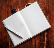 Abra um caderno e uma pena brancos vazios na madeira Imagens de Stock Royalty Free