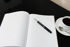 Abra um caderno, uma pena e uma xícara de café brancos vazios Foto de Stock