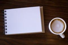 Abra un cuaderno blanco en blanco con café caliente en la tabla imágenes de archivo libres de regalías