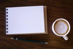 Abra un cuaderno blanco en blanco con café caliente en la tabla fotos de archivo