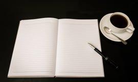 Abra un cuaderno, una pluma y una taza de café blancos en blanco Fotografía de archivo