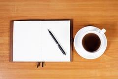 Abra un cuaderno, una pluma y una taza de café blancos en blanco Imagen de archivo