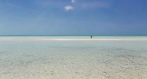 abra a vista da praia selvagem da ilha de cocos de Cayo do cubano com a turquesa, o oceano tranquilo e a pessoa indo distante par Imagem de Stock
