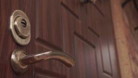 Abra y cierre la puerta con una cerradura de puerta dominante sobre el tirador de puerta almacen de metraje de vídeo