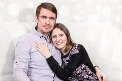 Abraçando os pares loving que sentam-se no sofá, jovens Imagens de Stock Royalty Free