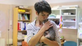 Abrace y los besos un gato en sus brazos antes de cirugía almacen de video