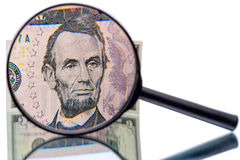Abraham Lincoln and magnifier. Abraham Lincoln in front of the five dollar banknote increased magnifier royalty free stock images