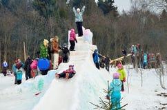 Abramtsevo, región de Moscú, Rusia, marzo, 13 2016 Los niños resbalan abajo la colina helada durante Bakshevskaya Shrovetide Foto de archivo libre de regalías