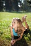 Abrandamento da menina que encontra-se na grama fresca fotografia de stock