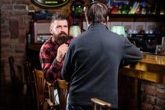 Abrandamento de sexta-feira no bar Amigos que relaxam no bar Conversação amigável com desconhecido Homem farpado brutal do modern fotografia de stock royalty free