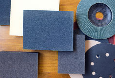 Abrasive materials - sheets of sandpaper and disks close-up Stock Images