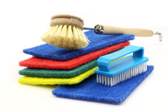 Abrasive pads and  two household brushes Stock Photos