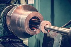 Abrasive wheel on the mandrel on the machine in front of the cylindrical part is ready for metal processing by grinding.  royalty free stock photography