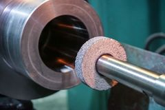 Abrasive wheel on the mandrel on the machine in front of the cylindrical part is ready for metal processing by grinding.  royalty free stock images