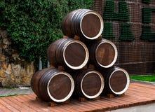 Abrau-Durso, hölzerne Weinfässer gebildet von einer Pyramide auf einer Plattform von Brettern, im Hintergrund eine Steinwand über stockfotos