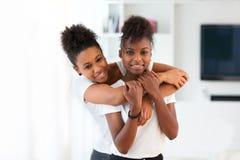 Abrazo afroamericano del retrato de los mejores amigos - personas negras Imagenes de archivo