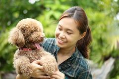 Abrazo asiático de la muchacha con su perro de caniche Imágenes de archivo libres de regalías