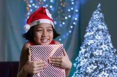 Abrazo asiático del niño una caja de regalo Fotos de archivo