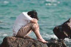 Abrazo asiático joven subrayado triste del hombre su rodilla que se sienta en la roca de la orilla de mar Imagen de archivo libre de regalías