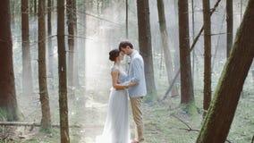 Abrazo casado del novio de la novia de la pareja que frota ligeramente otra situación en niebla del bosque en la boda del fondo almacen de video