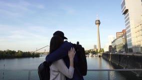 Abrazo caucásico feliz del beso de la reunión de los pares, torre de Rheinturm el Rin, Düsseldorf metrajes