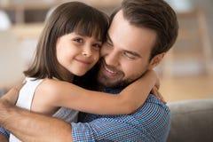 Abrazo de amor del pap? y de la hija en casa que hace la imagen fotos de archivo