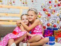 Abrazo de dos muchachas en los árboles de navidad Imágenes de archivo libres de regalías