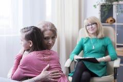Abrazo de la hija adolescente en el psicólogo Imagenes de archivo