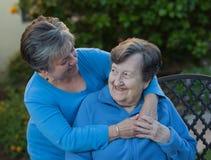 Abrazo de la hija y de la madre en el jardín Foto de archivo libre de regalías
