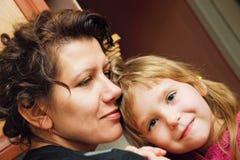 Abrazo de la mamá y de la hija en la cocina Fotos de archivo libres de regalías