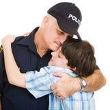 Abrazo de la policía y del muchacho fotografía de archivo