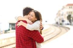 Abrazo de los pares feliz en una estación de tren Foto de archivo libre de regalías