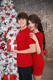 Abrazo de los pares de la feliz Navidad en ropa roja Soldado enrollado en el ejército moreno joven Fotos de archivo libres de regalías