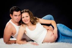 Abrazo de mentira de los pares del embarazo en un fondo negro Fotos de archivo