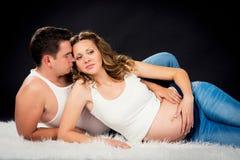 Abrazo de mentira de los pares del embarazo en un fondo negro Foto de archivo libre de regalías