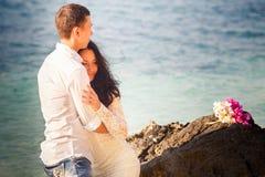 abrazo de novia y del novio en la roca Imagen de archivo libre de regalías