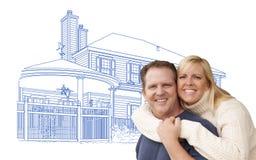 Abrazo de pares sobre el dibujo de la casa en blanco Foto de archivo